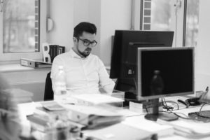 mężczyzna w białej koszuli pracuje na komputerze